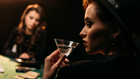 attractive girl drinking cocktail while playing poker at table in casino