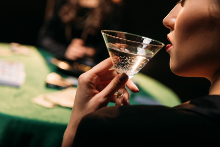 cropped image of girl drinking cocktail while playing poker at table in casino