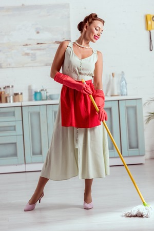 Smiling pin up cleaning kitchen floor with yellow mop