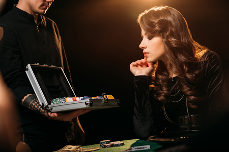 attractive girl looking at poker chips in box at table in casino 版權商用圖片