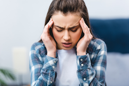 ill young woman suffering from headache at home