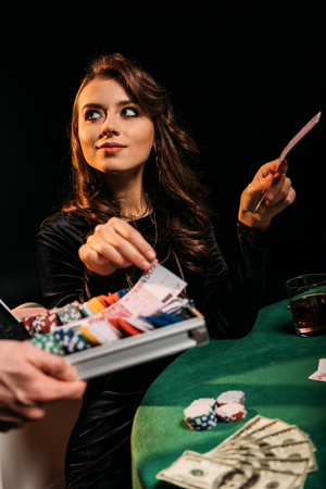 beautiful cheerful woman taking euro banknotes from box at table in casino Stock Photo