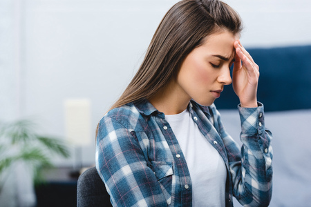 sick young woman suffering from headache at home