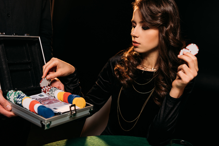 attractive girl taking poker chips from box at table in casino Stock Photo