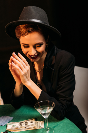 attractive smiling girl in hat sitting at poker table in casino, dollar banknotes and cocktail on tabletop Stock Photo