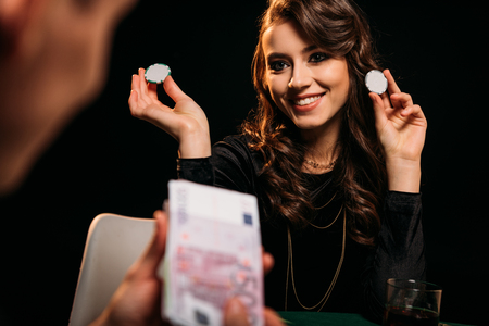 attractive smiling girl holding poker chips and looking at man at poker table in casino Stock Photo - 116291668