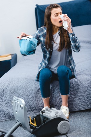 girl with allergy holding container from vacuum cleaner with dust and sneezing in bedroom Stock Photo
