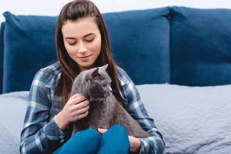 happy young woman stroking cute grey cat in bedroom