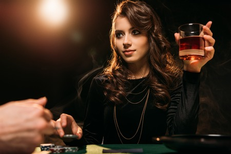 low angle view of attractive girl holding glass of whiskey at poker table in casino Stock Photo