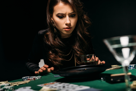 attractive concentrated girl looking at roulette at table in casino Stock Photo