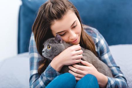 girl hugging adorable british shorthair cat in bedroom