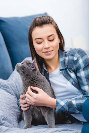 beautiful smiling girl lying on bed with adorable british shorthair cat Фото со стока