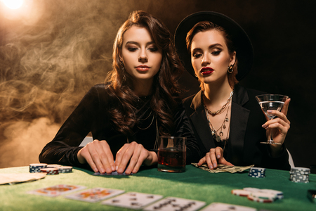 attractive girls in black clothes playing poker at table in casino