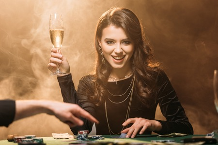 attractive happy girl holding glass of champagne at poker table in casino and looking at camera