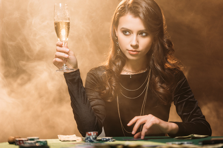 beautiful woman holding glass of champagne at poker table in casino and looking away