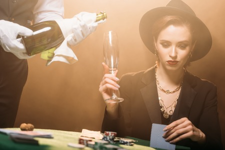 waiter pouring champagne in glass of attractive girl in jacket and hat in casino, she playing poker