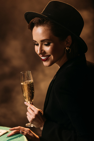smiling attractive girl in jacket and hat holding glass of champagne at poker table in casino