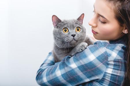 young woman holding beautiful grey british shorthair cat Standard-Bild - 116292035