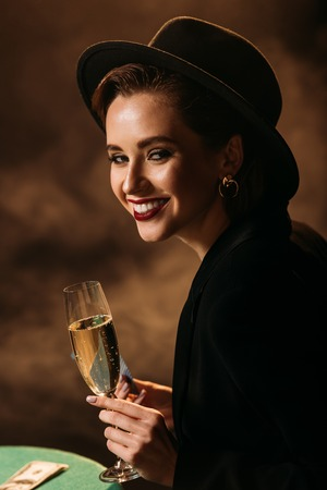 smiling attractive girl in jacket and hat holding glass of champagne at poker table in casino and looking at camera