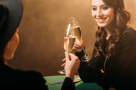 smiling attractive women clinking with glasses of champagne at poker table in casino