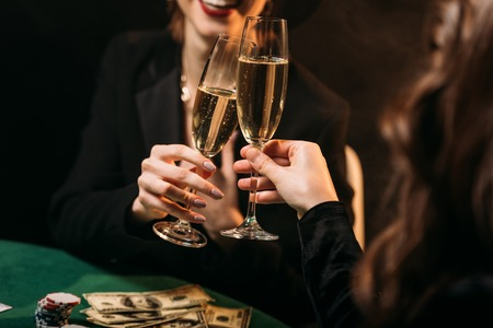 cropped image of happy girls clinking with glasses of champagne at poker table in casino
