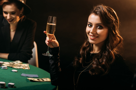 smiling attractive girl holding glass of champagne at poker table in casino and looking at camera Stock Photo