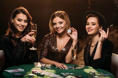 smiling attractive girls with glass of champagne, cigarette and poker chips sitting at table in casino Imagens