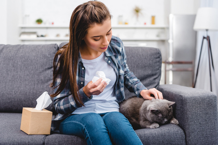 girl with allergy holding facial tissue and stroking cat on couch Stock Photo