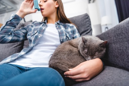 low angle view of woman using inhaler while sitting with cat on sofa Stock Photo