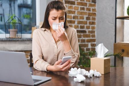 young businesswoman using smartphone and suffering from allergy at workplace