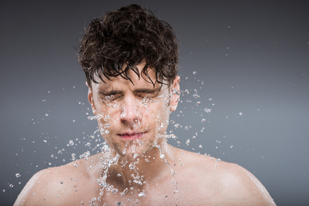 handsome man washing face with water drops, isolated on grey