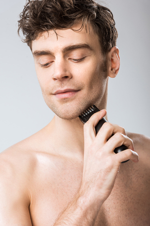 young man shaving with electric razor isolated on grey