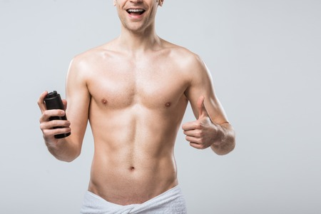 cropped view of shirtless man holding deodorant and showing thumb up, isolated on grey