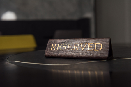 selective focus of reserved sign on black table in cafe Foto de archivo - 116292229