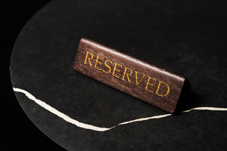 reserved sign on black table in cafe with copy space