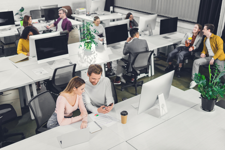 high angle view of young businessman and businesswoman using smartphone while colleagues sitting and working in office Foto de archivo - 116292637