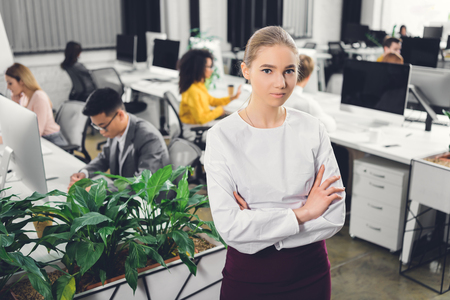beautiful young businesswoman standing with crossed arms and looking at camera in open space office Foto de archivo - 116292618