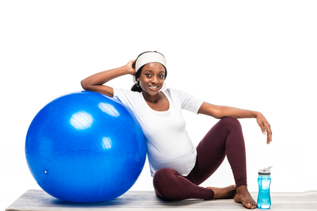 african american woman sitting on floor with fitness ball isolated on white