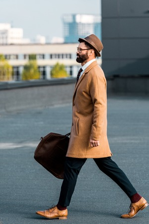 side view of bearded businessman with bag walking on roof