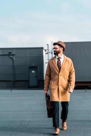 handsome businessman in beige coat with bag walking on roof