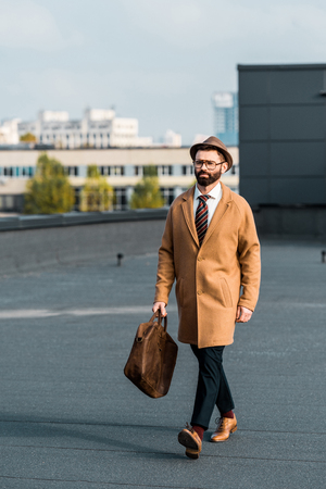 adult successful businessman in beige coat walking on roof Zdjęcie Seryjne - 116292790