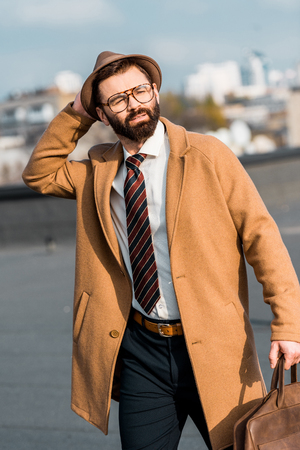 adult bearded businessman walking on roof and touching hat