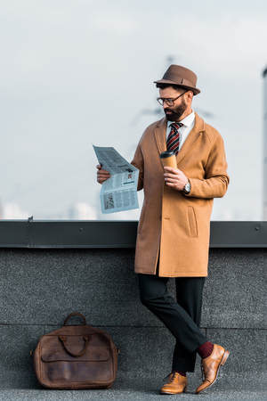 successful businessman with coffee to go reading newspaper
