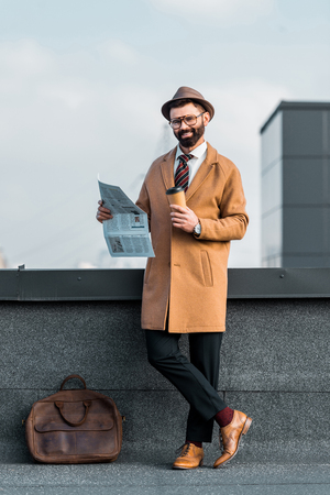 smiling bearded businessman standing with crossed legs while holding newspaper and coffee to go