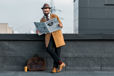 adult bearded man standing with crossed legs and reading business newspaper on roof