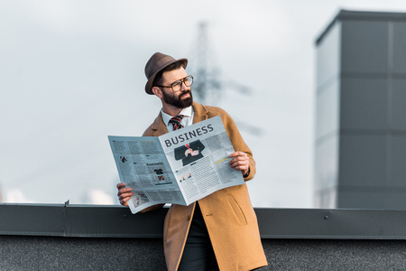 selective focus of handsome adult man in glasses with business newspaper