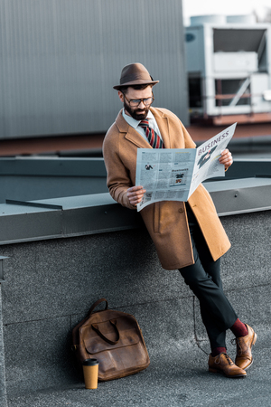 handsome man in coat and hat with crossed legs reading business newspaper Zdjęcie Seryjne