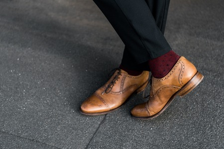 cropped view of male crossed legs in burgundy socks and oxford shoes