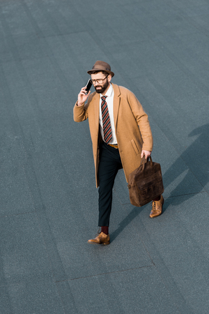 handsome businessman with bag walking and talking on smartphone Zdjęcie Seryjne - 116293129