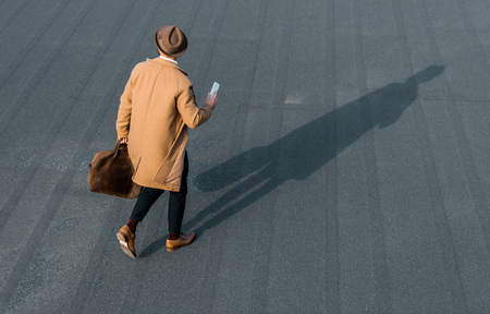 back view of businessman with bag and smartphone walking on roof Zdjęcie Seryjne - 116293130